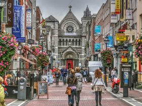 Famous shopping area in Dublin, Ireland.  Grafton Street showing shoppers, shops and church.